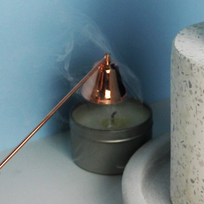 Snuffer - Rose Gold extinguishing a candle