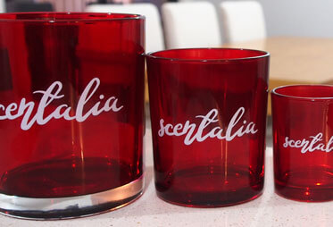 Adhesive labels in handwritten font on candle containers